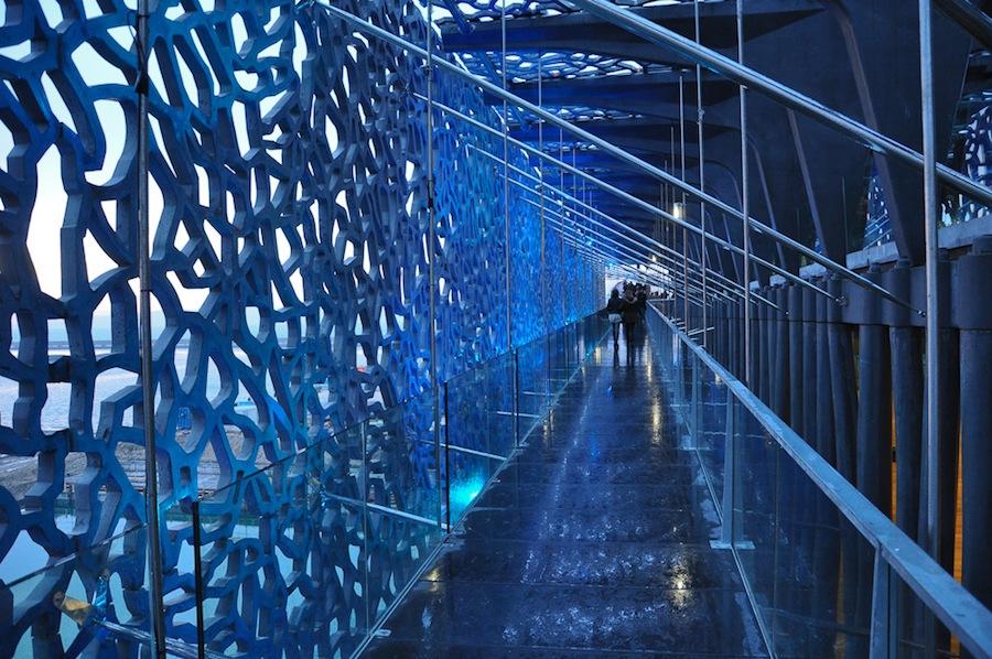 Impresionante vista de un corredor del Mucem, con el muro de rejilla por donde entra la luz tenue, diáfana. Foto de alex notag.
